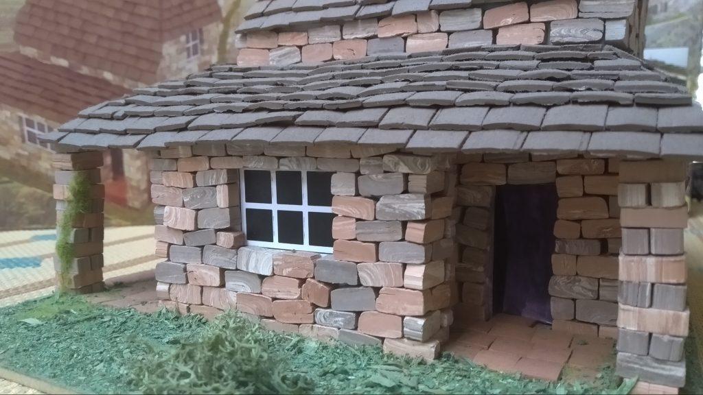 Fachada de una maqueta de casa de piedra